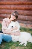 年轻行家妇女女孩白色羊羔皮狗剥去了牛仔裤 图库摄影