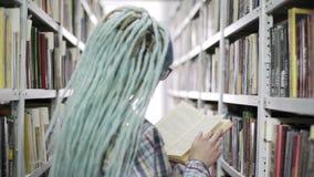 行家妇女看书在大学图书馆里,当站立在书架附近时 股票视频