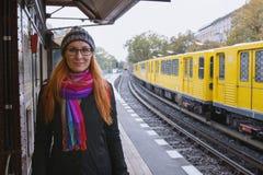 年轻行家妇女玻璃的和在火车站平台的warmclothes的 免版税库存图片