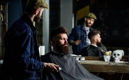 行家客户得到了新的理发 有看镜子,理发店背景的头发剪刀的理发师 专业大师 免版税库存图片