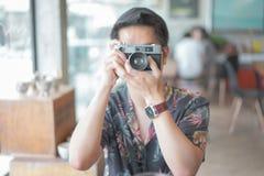行家少年采取在咖啡馆的一台影片照相机 免版税库存照片