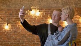 行家年轻有吸引力的夫妇在智能手机做selfie,通信构想,砖背景 股票录像