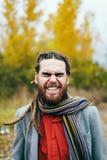 行家微笑着 有dreadlocks的一个时髦的在一件红色衬衣和灰色夹克的人和胡子 摆在自然的新郎 库存图片