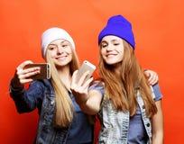 行家成套装备的两个十几岁的女孩朋友在pho做selfie 库存图片