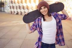 行家成套装备的深色的十几岁的女孩(牛仔裤短缺, keds、格子花呢上衣,帽子)有在户外公园的一个滑板的 库存照片