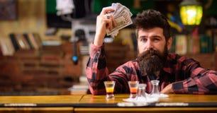 行家拿着金钱,计数现金买更多酒精 免版税库存照片
