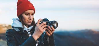 行家旅游女孩举行在手上在现代照片照相机,在照相机技术,旅途的摄影师神色采取摄影点击 库存照片