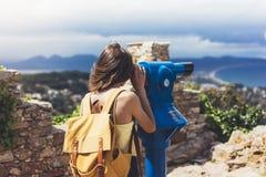 行家旅游看起来敏锐双筒望远镜在全景,生活方式概念旅行,有背包的旅客挤撞在backgroun 免版税库存图片