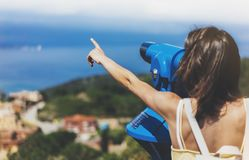 行家旅游看起来敏锐双筒望远镜在全景,生活方式概念旅行,有背包的旅客挤撞在backgroun 图库摄影