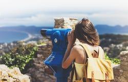 行家旅游看起来敏锐双筒望远镜在全景,生活方式概念旅行,有背包的旅客挤撞在backgroun 免版税库存照片