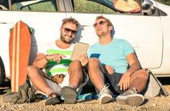 年轻行家最好的朋友获得与片剂的乐趣在汽车旅行 免版税库存图片