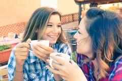 年轻行家最好的朋友获得谈论闲话在早餐期间在酒吧-每日片刻生活和技术的概念的乐趣 免版税库存照片