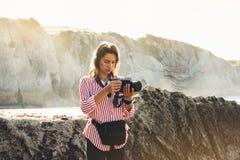 行家有拍惊人的海景日落的照片在照相机在背景山,摄影师enjoyi的背包的远足者游人 图库摄影