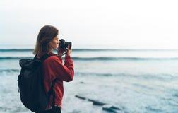 行家有拍惊人的海景日落的照片在照相机的背包的远足者游人在背景蓝色海,摄影师enjoyin 免版税库存照片