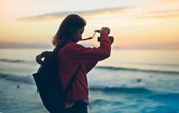 行家有拍惊人的海景日落的照片在照相机的背包的远足者游人在背景蓝色海,摄影师enjoyin 库存照片