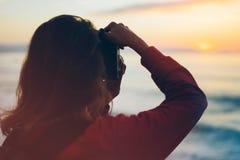 行家有拍惊人的海景日落的照片在照相机的背包的远足者游人在背景蓝色海,摄影师enjoyin 免版税图库摄影