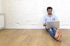 行家现代便装样式看起来的年轻人坐客厅研究膝上型计算机的家地板 免版税库存照片