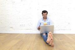 行家现代便装样式看起来的年轻人坐客厅研究膝上型计算机的家地板 免版税库存图片