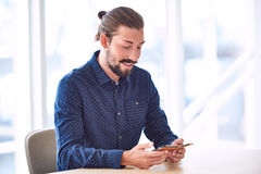 行家用使用他的电话的人小圆面包供以座位在桌上 免版税库存照片