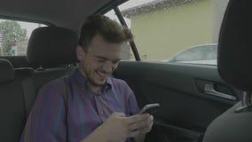 行家聊天和发短信在触摸屏幕的年轻人乘客使用他的大声笑滑稽在uber出租汽车汽车的智能手机 影视素材