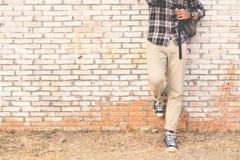 行家脚一双人和牛仔裤运动鞋在老墙壁 免版税图库摄影