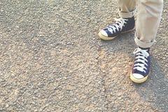 行家脚一双人和牛仔裤运动鞋本质上 免版税库存图片