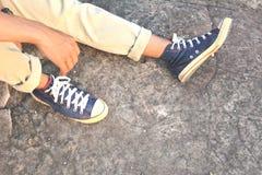 行家脚一双人和牛仔裤运动鞋本质上 免版税库存照片