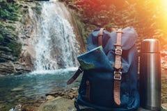 行家蓝色背包、地图和热水瓶特写镜头 从前面旅游旅客袋子的看法在瀑布背景 远足骗局的冒险 免版税库存图片