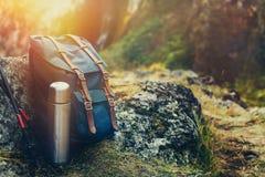 行家蓝色背包、热水瓶和迁徙的波兰人特写镜头,正面图 在岩石背景的旅游旅客袋子 冒险暴涨 免版税库存图片