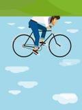 行家骑在天空的一辆自行车 免版税库存照片