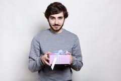 行家年轻有胡子的人在拿着在白色背景的灰色毛线衣穿戴了一件被包裹的礼物 恋人的一个礼物盒 g 库存照片