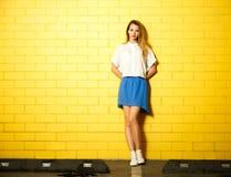 行家黄色墙壁的时尚女孩 免版税库存照片