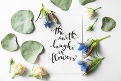 行情`在与叶子和花的纸写的花`的地球笑在白色背景 顶视图 库存照片