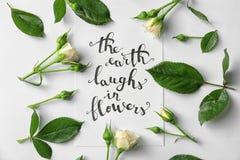 行情`在与玫瑰和叶子的纸写的花`的地球笑在白色背景 顶视图 库存照片