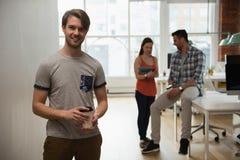 行政举行的咖啡杯画象,当同事谈论在背景时 免版税库存照片