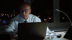 行政商人佩带的玻璃和研究在工作场所的膝上型计算机在晚上 股票视频