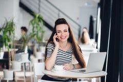 行政妇女在网上微笑和与膝上型计算机一起使用,当谈话在咖啡馆时的电话 免版税库存照片