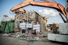 行星保存 拿着标志的小孩站立在巨大的废品旧货栈 免版税库存照片