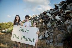 行星保存 拿着标志的小孩站立在巨大的废品旧货栈 库存图片