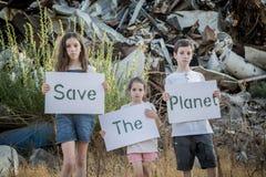 行星保存 拿着标志的小孩站立在巨大的废品旧货栈 库存照片