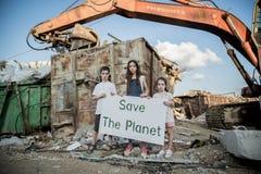 行星保存 拿着标志的小孩站立在巨大的废品旧货栈 图库摄影