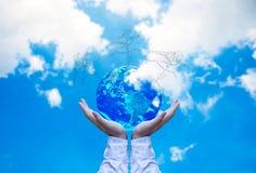 行星和树在人移交蓝天与白色云彩,保存地球概念 库存图片