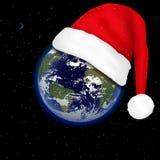 行星地球上的圣诞老人帽子 库存图片