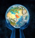 行星地球上的沙特阿拉伯在手上 免版税库存图片