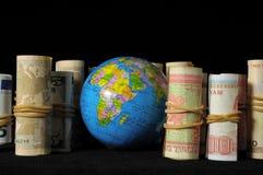行星地球和滚动的金钱 免版税库存图片