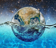 行星地球在满天星斗的天空的背景的水中被淹没 库存图片