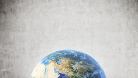 行星地球对混凝土墙,底部的屏幕 库存图片
