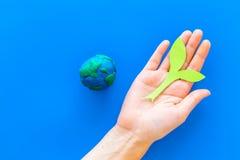 行星,生态 行星地球在蓝色背景顶视图的地球和植物coutout的plastiline标志复制空间 免版税库存图片