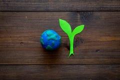 行星,生态 行星地球在黑暗的木背景顶视图的地球和植物coutout的plastiline标志复制空间 免版税库存照片