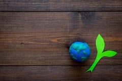 行星,生态 行星地球在黑暗的木背景顶视图的地球和植物coutout的plastiline标志复制空间 库存照片